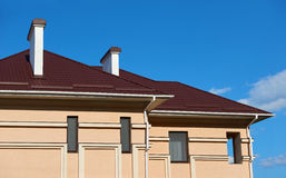Asphaltieren Sie Dach und Wände des neuen Privathauses, mit Kaminen und Belüftung auf dem Hintergrund des Himmels, Baukonzept, Fa Lizenzfreies Stockfoto