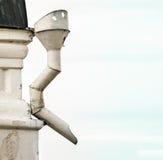 Asphaltieren Sie den Abwasserkanal, der zur Ecke des weißen Gebäudes befestigt wird. Stockbild