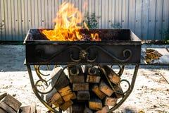 Asphaltieren Sie den Grill, geschmiedet, handgemacht, mit einem Muster Ein heißes Feuer auf dem Holz mit Rauche für Grill und geg stockfoto