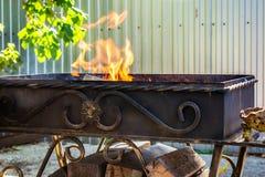 Asphaltieren Sie den Grill, geschmiedet, handgemacht, mit einem Muster Ein heißes Feuer auf dem Holz mit Rauche für Grill und geg stockbild