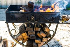 Asphaltieren Sie den Grill, geschmiedet, handgemacht, mit einem Muster Ein heißes Feuer auf dem Holz mit Rauche für Grill und geg lizenzfreies stockbild