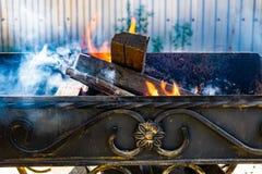 Asphaltieren Sie den Grill, geschmiedet, handgemacht, mit einem Muster Ein heißes Feuer auf dem Holz mit Rauche für Grill und geg lizenzfreie stockbilder