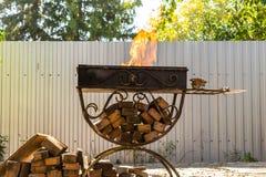 Asphaltieren Sie den Grill, geschmiedet, handgemacht, mit einem Muster Ein heißes Feuer auf dem Holz mit Rauche für Grill und geg lizenzfreie stockfotografie