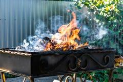Asphaltieren Sie den Grill, geschmiedet, handgemacht, mit einem Muster Ein heißes Feuer auf dem Holz mit Rauche für Grill und geg lizenzfreie stockfotos