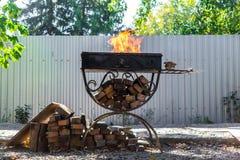 Asphaltieren Sie den Grill, geschmiedet, handgemacht, mit einem Muster Ein heißes Feuer auf dem Holz mit Rauche für Grill und geg stockbilder