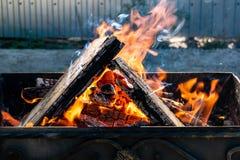 Asphaltieren Sie den Grill, geschmiedet, handgemacht, mit einem Muster Ein heißes Feuer auf dem Holz mit Rauche für Grill und geg stockfotos