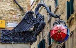 Asphaltieren Sie den Vogel, der rote blaue und grüne Regenschirmlampe in Venedig, I hält Lizenzfreie Stockfotografie