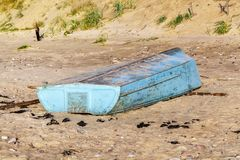 Asphaltieren Sie Fischerboot auf sandigem Strand nahe Meer Lizenzfreie Stockfotografie