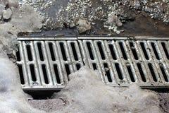 Asphaltieren Sie Gitter der Wasserentwässerung unter dem schmelzenden Schnee Lizenzfreie Stockfotos