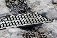 Asphaltieren Sie Gitter der Wasserentwässerung unter dem schmelzenden Schnee Stockfotografie