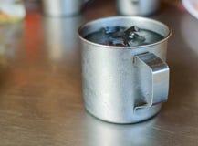 Asphaltieren Sie Glas oder Schale kaltes Wasser mit Eis auf Edelstahltabellenhintergrund Stockfoto