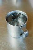 Asphaltieren Sie Glas oder Schale kaltes Wasser mit Eis auf Edelstahltabellenhintergrund Lizenzfreies Stockbild