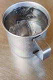 Asphaltieren Sie Glas oder Schale kaltes Wasser mit Eis auf Edelstahlvorsprung Stockfotografie
