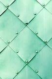 Asphaltieren Sie grüne Oberfläche von alten gehämmerten Metallplatten mit Nieten auf ihnen Lizenzfreie Stockfotografie