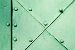 Asphaltieren Sie grüne Oberfläche von alten gehämmerten Metallplatten mit Nieten auf ihnen Lizenzfreies Stockfoto