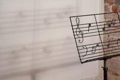 Asphaltieren Sie Handwerkernotenpult mit gezogenen musikalischen Anmerkungen, mit einem Schatten des Personals von Musik Stockfoto