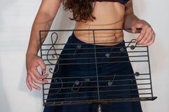 Asphaltieren Sie Handwerkernotenpult mit gezogenen musikalischen Anmerkungen, mit Mädchenhintergrund Stockfotografie