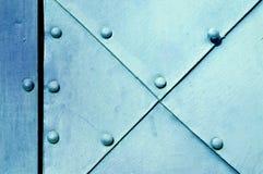 Asphaltieren Sie hellblaue strukturierte Oberfläche von alten gehämmerten Metallplatten mit Nieten auf ihnen Stockfotografie