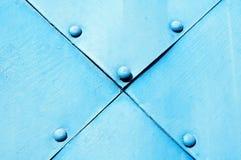 Asphaltieren Sie hellblaue strukturierte Oberfläche von alten gehämmerten Metallplatten mit Nieten auf ihnen Lizenzfreies Stockbild