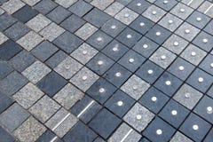 Asphaltieren Sie Kennzeichen in der Straße für blinde Personen Stockfoto