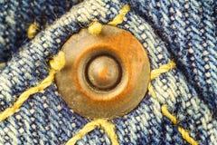 Asphaltieren Sie Knopf auf Blue Jeans, hohes Bild der linearen Wiedergabe Makro Lizenzfreie Stockfotos