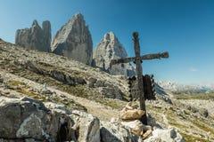 Asphaltieren Sie Kreuz und den Hintergrund Tre Cimes Tre Cime di Lavaredo mit schönem blauem Himmel, Stockfoto