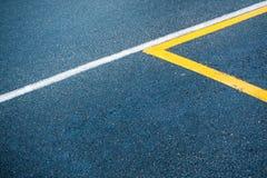 Asphaltieren Sie Oberfläche mit den weißen und gelben Linien lizenzfreies stockfoto