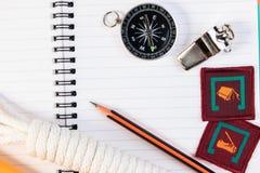 Asphaltieren Sie Pfeife, Pfadfinderseil, Notizbuch, Kompass, Ausweis und Bleistift O Stockfotografie