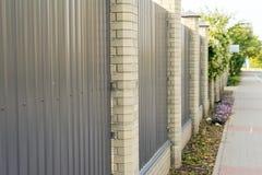 Asphaltieren Sie privaten Bereich des Zauns mit Spalten des Ziegelsteines stockbilder