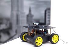 Asphaltieren Sie Roboter mit gelben Rädern auf einer weißen Tabelle Lizenzfreie Stockbilder