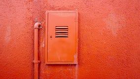 Asphaltieren Sie Rohr und elektrischen Kasten auf orange Farbwand Stockfoto