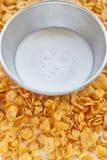 Asphaltieren Sie Schüssel mit Milch auf einem gemalten weißen hölzernen Hintergrund Corn-Flakes zerstreut auf einen Holztisch stockfotos