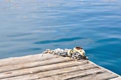 Asphaltieren Sie Schiffsketten und -schiffspoller auf hölzernem Pier Stockbilder