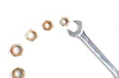 Asphaltieren Sie Schlüssel und viele verrosteten Nüsse auf Weiß Stockbild