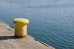 Asphaltieren Sie Stange, um Boot auf dem Pier zu binden Stockfoto