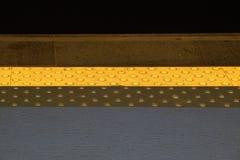 Asphaltieren Sie Taststreifen mit einer gelben Linie - für sehbehindertes behindertes und Leute mit Blindheit - auf Lizenzfreie Stockfotografie