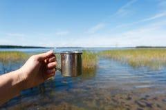 Asphaltieren Sie touristische Teeschale in der Mannhand auf Hintergrund im Freien Stockbild