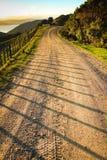 Asphaltierte Landstraße mit Taktstock- und Drahtzaun, Mahia-Halbinsel, Nordinsel, Neuseeland Lizenzfreie Stockfotos