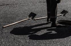 Asphaltierung laufend, Arbeitskraftfüße und Schaufeln Lizenzfreie Stockfotos