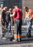 Asphalting in progress group workers with shovels Royalty Free Stock Photo