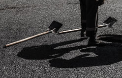 Asphalting in progress, worker feet and shovels Royalty Free Stock Photos