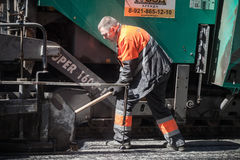 Asphalting in progress, worker with a shovel Royalty Free Stock Photography