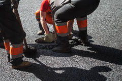 Asphalting in progress, workers install manhole Royalty Free Stock Images