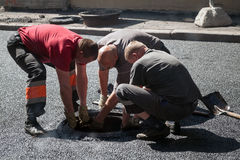 Asphalting in progress, workers install sewer manhole Royalty Free Stock Photos