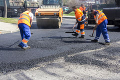 Asphalting and Repair of roads. Workers on Asphalting paver machine during Road street repairing works Stock Image
