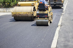 Asphalting roads. Compactor roller during road construction at asphalting work Royalty Free Stock Photo
