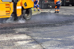 Asphalting roads. Roller and workers on asphalting and repair of city streets Royalty Free Stock Images