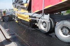 Asphalting. Tracked paver laying fresh asphalt pavement Stock Photos