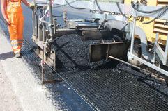 Asphalting. Tracked paver laying fresh asphalt pavement Royalty Free Stock Images