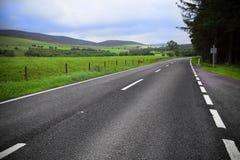 Asphaltstraße durch das grüne Feld und Wolken auf blauem Himmel Stockfotografie